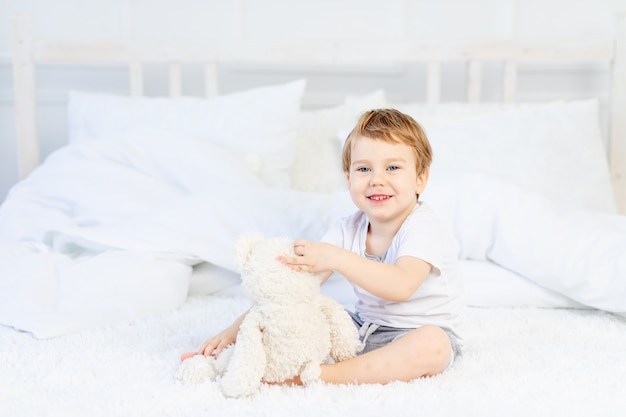 Un enfant avec un ours en peluche sur le lit à la maison joue et rit.