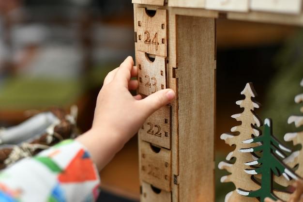 Un enfant ouvre le calendrier de l'avent en bois avec des cadeaux