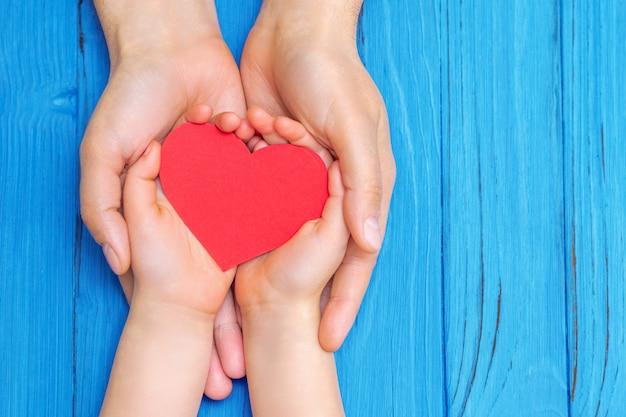 Enfant et papa mains tenant coeur rouge.