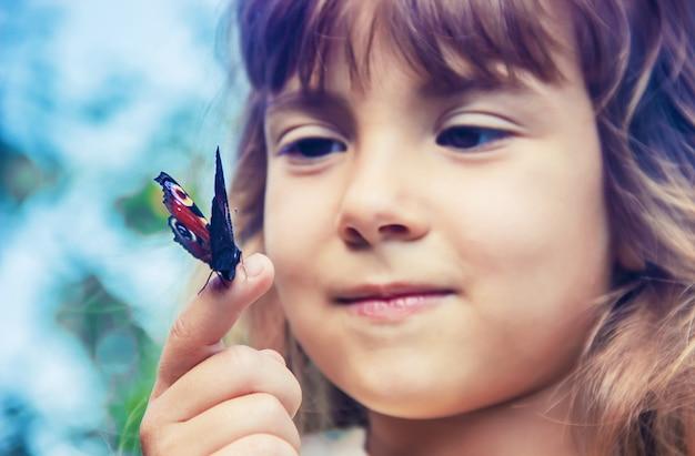 Enfant avec un papillon dans ses mains.
