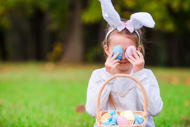 Enfant à pâques en jouant avec des oeufs en plein air