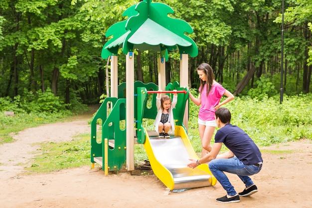 Enfant avec parents à l'aire de jeux. maman, papa et fille. jouer en famille.