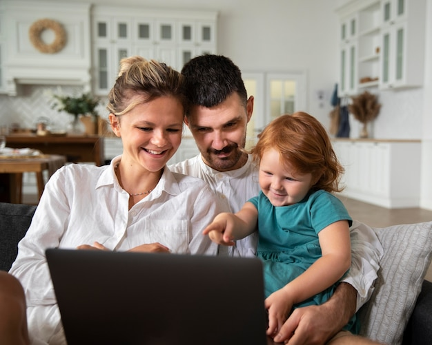 Enfant et parents de coup moyen avec ordinateur portable