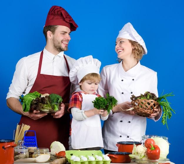 Enfant avec les parents cuisinant à la table de la cuisine famille aimante heureuse préparant le dîner ensemble joyeux
