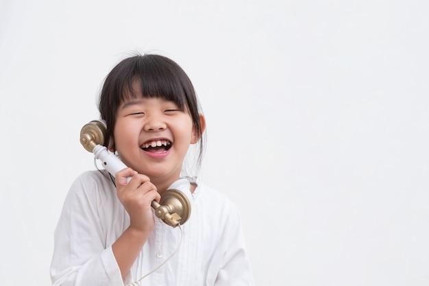L'enfant passe un bon moment avec lui au téléphone.