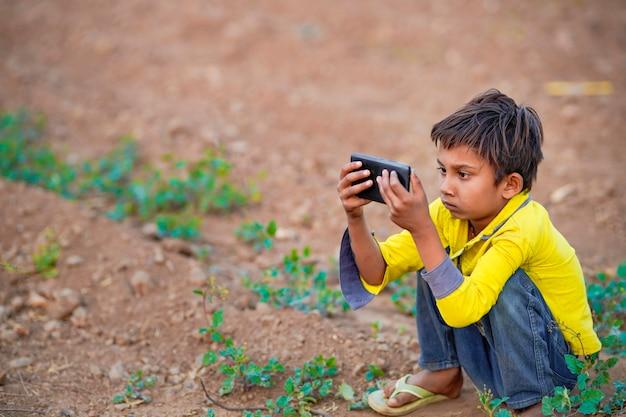Enfant pauvre indien jouant avec un mobile sur le terrain agricole. scène rurale.