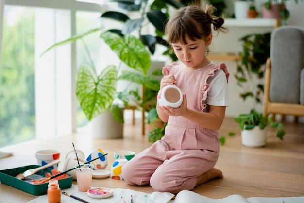Enfant peignant un passe-temps de bricolage à la maison en pot de plante