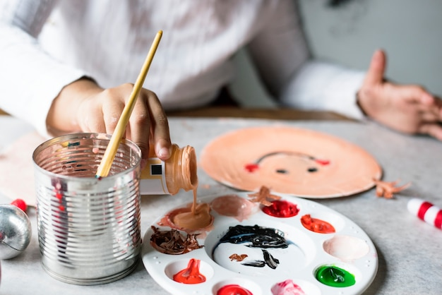 Enfant peignant le père noël sur une assiette en papier