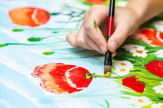 L'enfant peint des coquelicots et des camomilles à la gouache