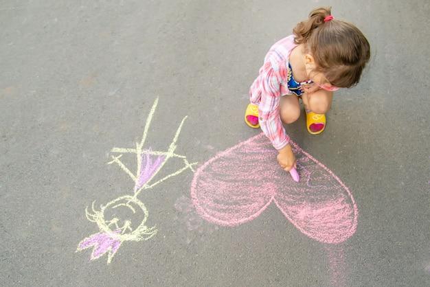 L'enfant peint à la craie sur le cœur d'asphalte.