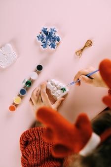 L'enfant peint des jouets de noël. vue de dessus