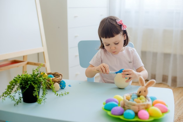 Enfant peint des œufs sur des œufs de pièce en bois