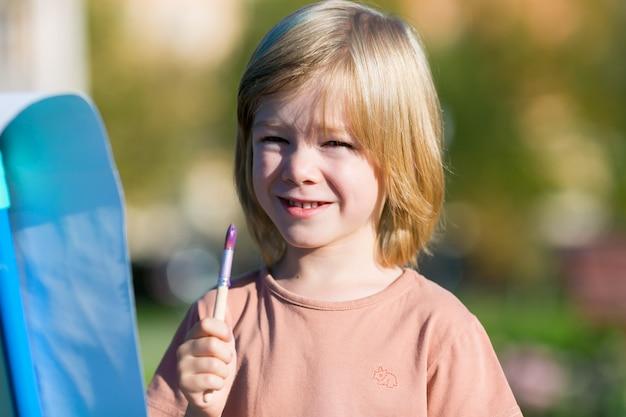 Enfant peint ses premiers tableaux au pinceau et à la peinture.