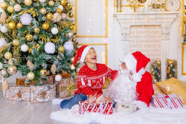 Un enfant et le père noël rient près de l'arbre de noël, un enfant heureux parle au père noël