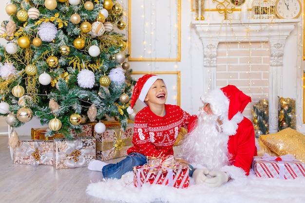 L'enfant et le père noël rient près de l'arbre de noël, un enfant heureux parle au père noël