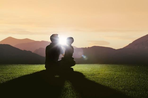 L'enfant et le père s'assoient sur la montagne rencontrant l'aube du soleil