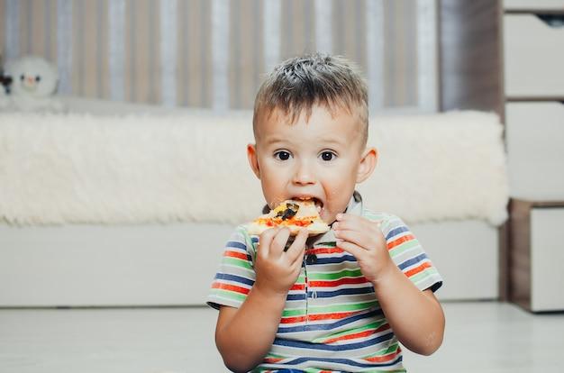 L'enfant, une petite fille assise sur le sol et s'amusant à manger de la pizza