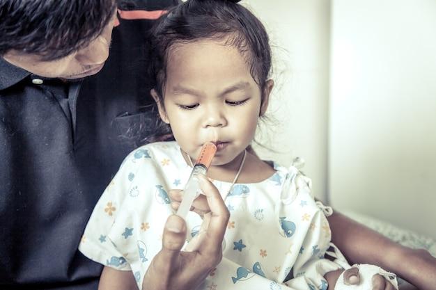 Enfant petite fille obtient des médicaments avec une seringue dans sa bouche dans le ton de couleur vintage