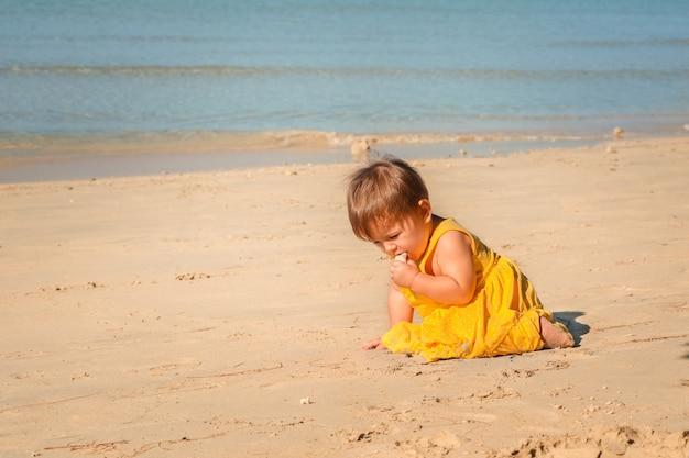 Enfant sur la plage jouant dans le sable.