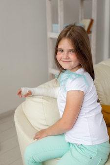 Enfant avec un plâtre sur un poignet ou un bras cassé souriant et s'amusant sur un canapé. attitude positive