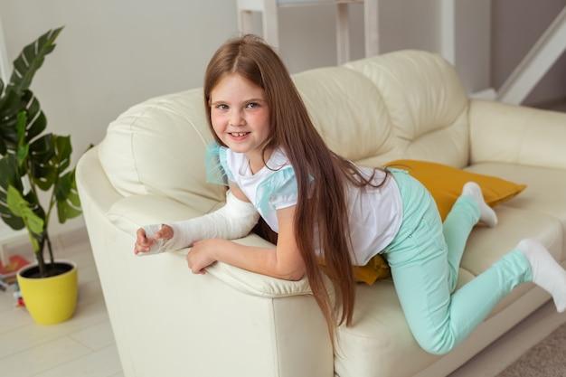 Enfant avec un plâtre sur un poignet ou un bras cassé souriant et s'amusant sur un canapé attitude positive