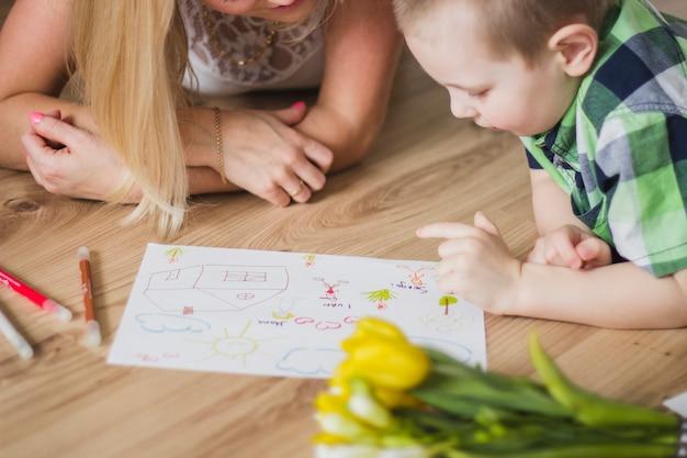 Enfant pointant vers un dessin à côté de sa mère