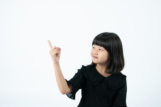 L'enfant pointe son doigt vers le fond blanc.