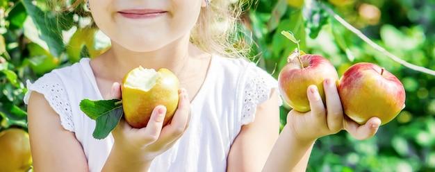 Enfant avec une pomme. mise au point sélective. jardin.