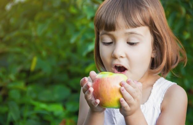 Enfant avec une pomme. mise au point sélective. la nature