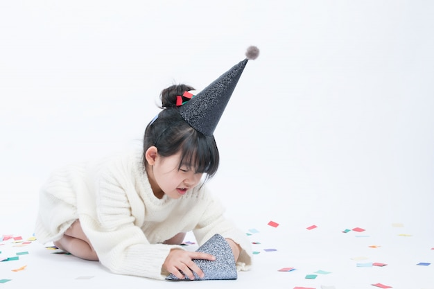 L'enfant portant un chapeau de fête noir s'amuse. fond blanc et chapeau noir vont bien ensemble.