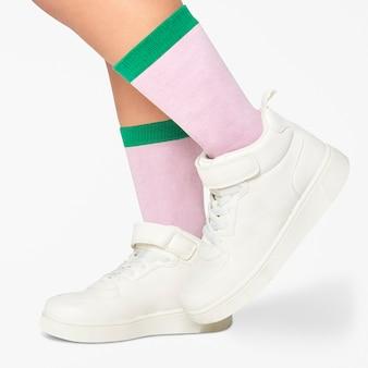 Enfant portant des chaussettes roses à rayures vertes, des baskets blanches