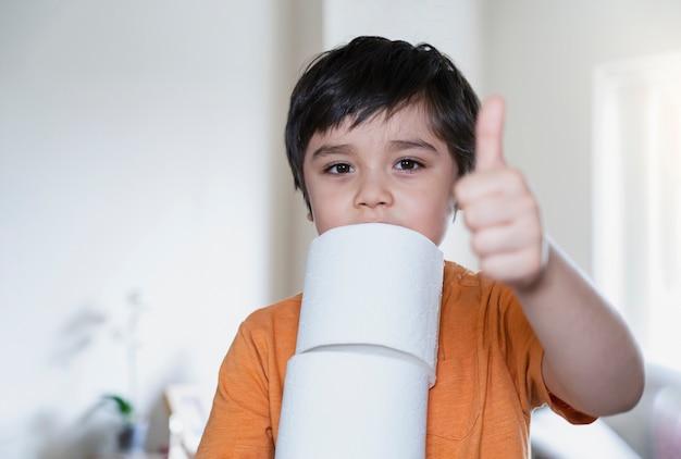 Enfant portant une pile de papier toilette avec salon flou, mise au point sélective enfant garçon tenant le rouleau de papier toilette montrant les pouces vers le haut, soins de santé pour enfants