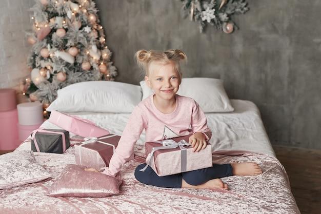 Enfant portant un pyjama et ouvrant le cadeau de noël