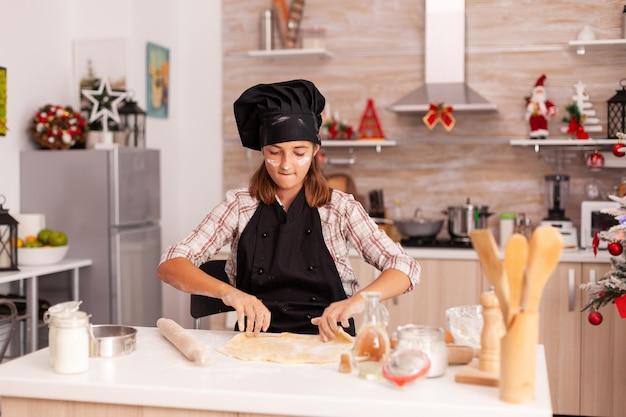 Enfant portant un tablier de cuisson mettant de la farine sur de la pâte maison