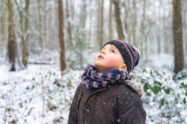 Enfant portant des vêtements chauds restant dans un parc en hiver et regardant avec rêverie. petit garçon attendant un miracle de noël. première neige dans la forêt.