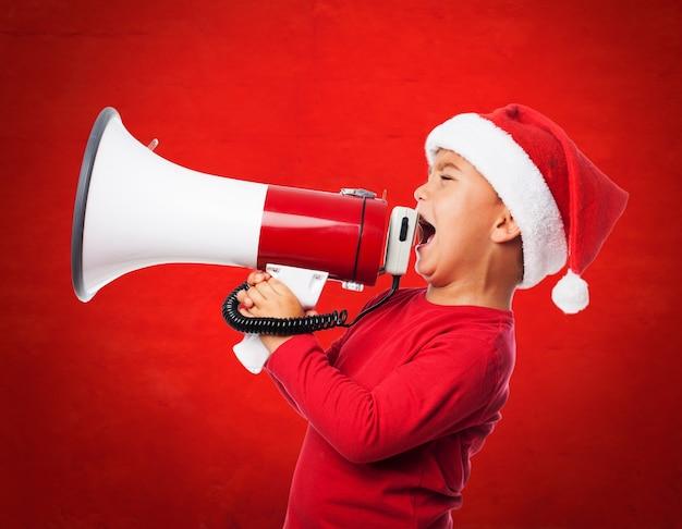 Un enfant porte le chapeau de santa et crier avec un mégaphone