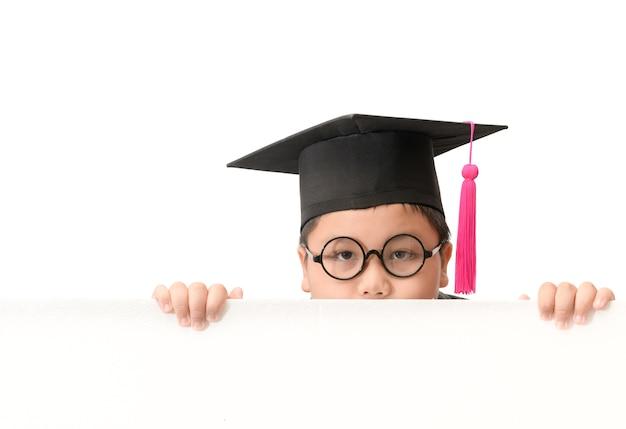 Enfant porter le chapeau de graduation se cacher derrière le panneau de bannière blanc
