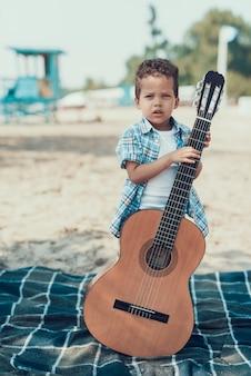 Enfant pose avec une guitare acoustique