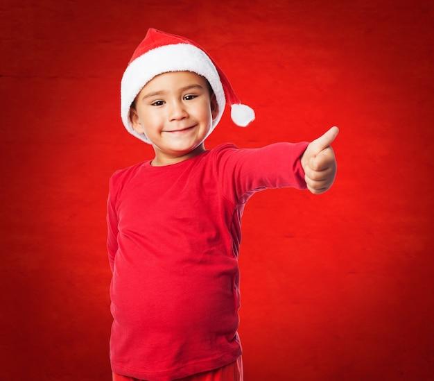 Enfant avec le pouce et fond rouge
