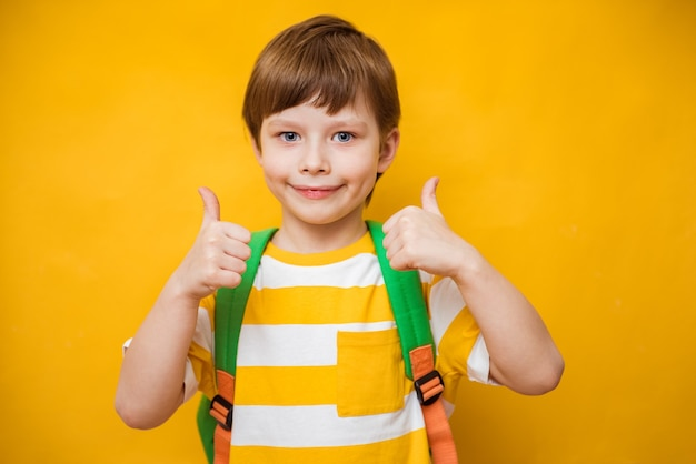 Enfant avec les pouces vers le haut sur fond jaune