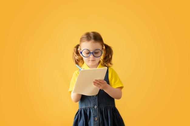 Enfant prenant des notesrêves d'enfants isolés sur fond jaune contexte de l'éducation kid retour à l'école
