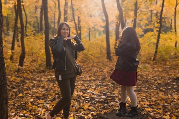 Enfant prenant une photo de sa mère sur un appareil photo rétro en automne parc passe-temps et loisirs concept