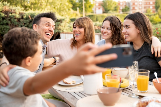 Enfant prenant selfie de famille en train de déjeuner dehors ensemble