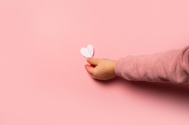 L'enfant prend une carte de la saint-valentin en papier sur fond rose. composition saint-valentin. bannière. mise à plat, vue de dessus.