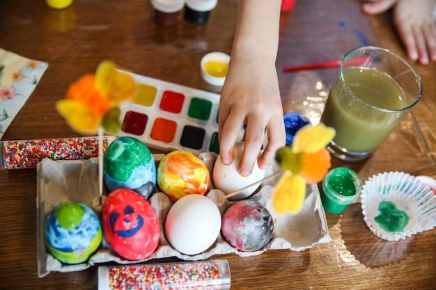 L'enfant prend un œuf du support d'artisanat sur la table pour la décoration de pâques
