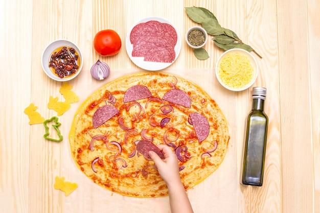 L'enfant prépare la pizza étape par étape