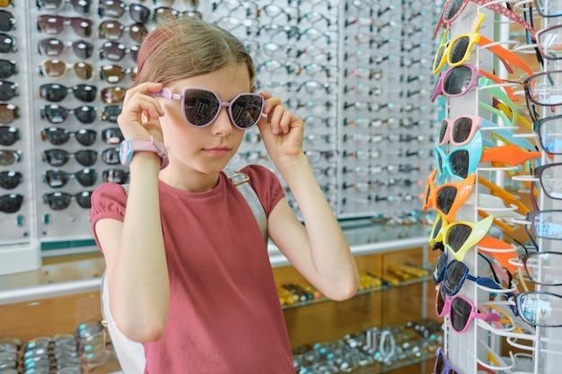 Enfant près de vitrine en magasin de lunettes