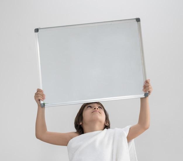 Enfant prêt pour le pèlerinage tenant un tableau de l'espace de copie