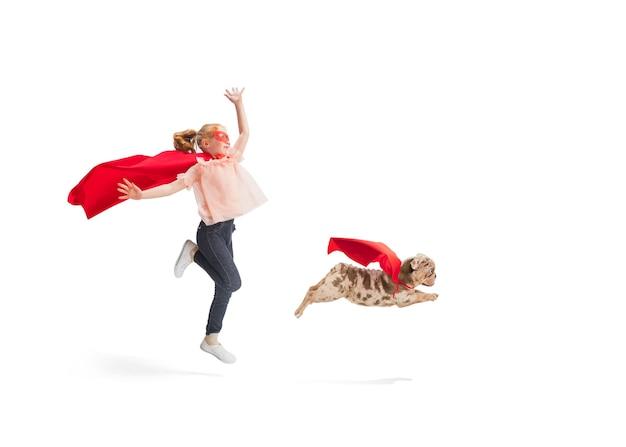 Enfant prétendant être un super-héros avec son super chien en manteaux rouges isolé sur fond de studio blanc. rêves, émotions, amour et amitié des animaux de compagnie, concept de motivation. puissant ensemble. espace de copie.