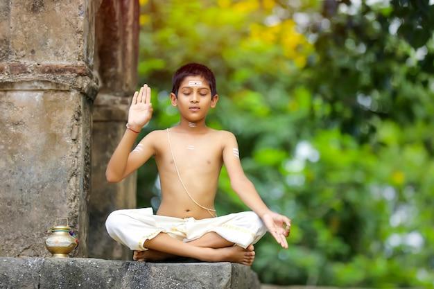L'enfant prêtre indien faisant la méditation